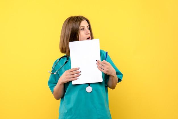 Widok z przodu kobieta lekarz posiadający pliki na żółtej podłodze szpital medyczny kolor