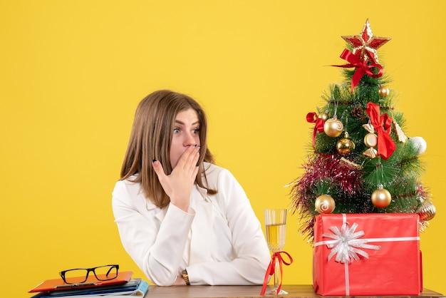 Widok z przodu kobieta lekarz siedzi przed stołem na żółtym tle z choinką i pudełkami na prezenty