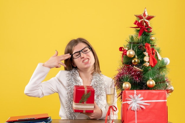 Widok z przodu kobieta lekarz siedzi przed stołem z prezentami i drzewem na żółtym tle z choinką i pudełkami na prezenty