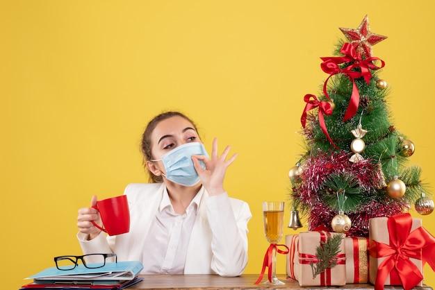 Widok z przodu kobieta lekarz siedzi w masce ochronnej na żółtym tle z choinką i pudełkami na prezenty