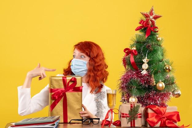 Widok z przodu kobieta lekarz siedzi w masce z prezentami świątecznymi i drzewem na żółtym tle