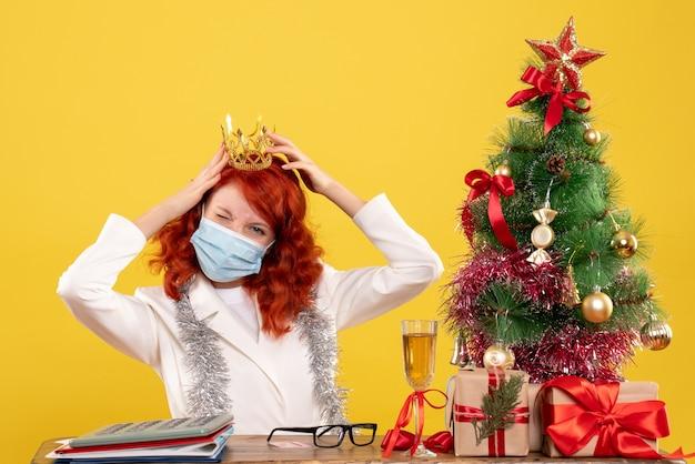 Widok z przodu kobieta lekarz siedzi w masce z prezentami święta noszenia korony na żółtym tle
