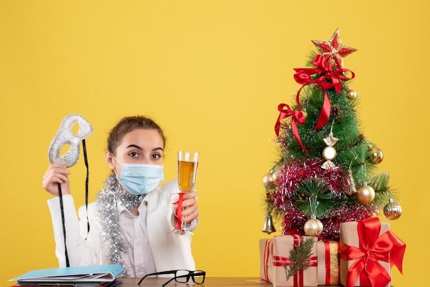 Widok z przodu kobieta lekarz siedzi w sterylnej masce trzymając szampana na żółtym tle