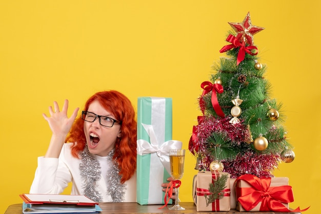 Widok z przodu kobieta lekarz siedzi z prezentami świątecznymi i drzewem na żółtym tle