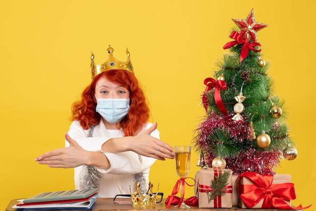 Widok z przodu kobieta lekarz siedzi z prezentami świątecznymi i nosząc koronę na żółtym tle