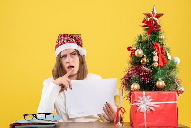 Widok z przodu kobieta lekarz siedzi z prezentami świątecznymi posiadania dokumentów na żółtym tle