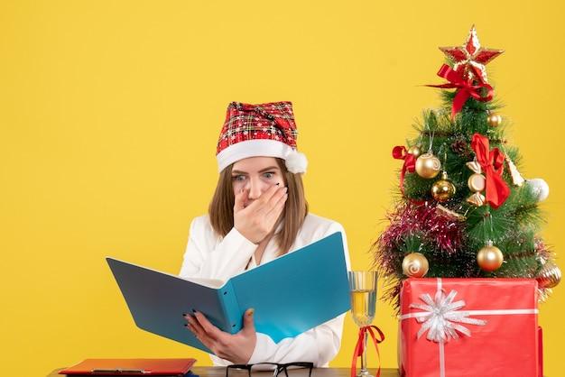 Widok z przodu kobieta lekarz siedzi z prezentami świątecznymi, trzymając pliki na żółtym tle
