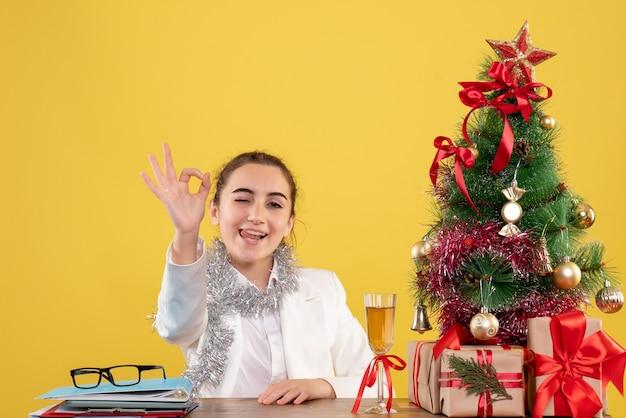 Widok z przodu kobieta lekarz siedzi za stołem na żółtym tle z choinką i pudełkami na prezenty
