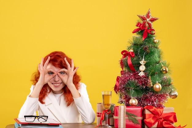 Widok z przodu kobieta lekarz siedzi za stołem z prezentami świątecznymi i drzewem na żółtym tle