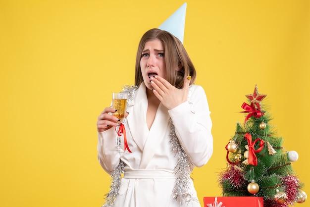 Widok z przodu kobieta lekarz trzymając kieliszek szampana i obchodzi