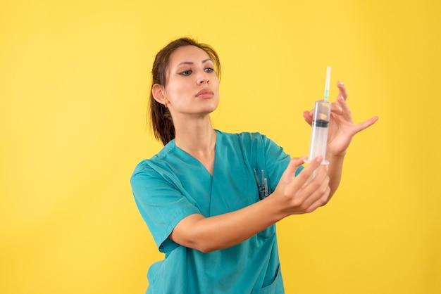 Widok z przodu kobieta lekarz trzymając zastrzyki na żółtym tle