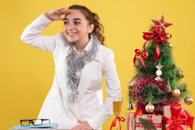 Widok z przodu kobieta lekarz uśmiechając się i patrząc na odległość na żółtym tle z choinką i pudełkami na prezenty