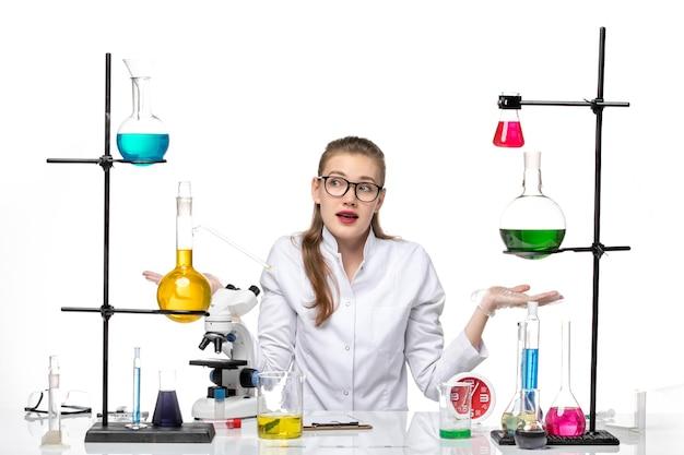 Widok z przodu kobieta lekarz w białym garniturze medycznym siedzi przed stołem z roztworami na białym tle wirus covid pandemia chemia