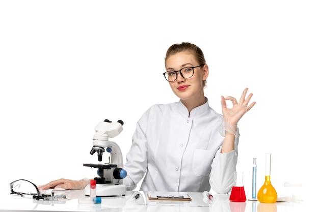 Widok z przodu kobieta lekarz w białym garniturze medycznym siedzi przed stołem z rozwiązaniami na białej przestrzeni