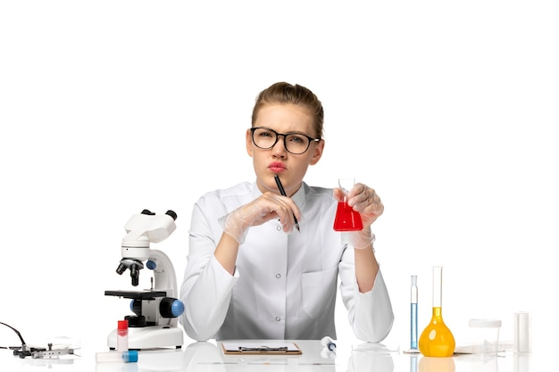 Widok z przodu kobieta lekarz w białym garniturze medycznym w rękawiczkach, trzymając kolbę z roztworem na białej przestrzeni
