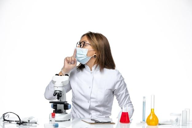 Widok z przodu kobieta lekarz w białym kombinezonie medycznym i masce z powodu covid na białej przestrzeni