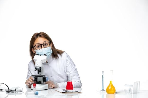 Widok z przodu kobieta lekarz w białym kombinezonie medycznym z maską z powodu covid przy użyciu mikroskopu na białej przestrzeni