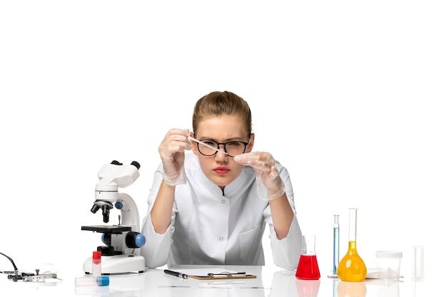 Widok z przodu kobieta lekarz w garniturze medycznym w rękawiczkach, pracująca z roztworami na białym biurku