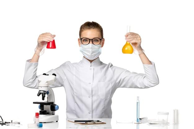 Widok z przodu kobieta lekarz w kombinezonie medycznym w masce z powodu covid pracy z rozwiązaniami na białym biurku