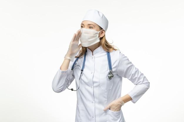 Widok z przodu kobieta lekarz w kombinezonie medycznym z maską i rękawiczkami z powodu koronawirusa na białej ścianie choroba pandemia zdrowia - wirus