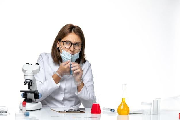 Widok z przodu kobieta lekarz w kombinezonie medycznym z maską z powodu covid pracy z roztworami na białym biurku