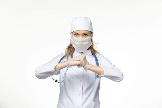 Widok z przodu kobieta lekarz w kombinezonie medycznym ze sterylną maską z powodu koronawirusa na białej ścianie choroby pandemicznej zdrowia
