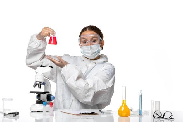 Widok z przodu kobieta lekarz w kombinezonie ochronnym i masce trzymającej kolbę z czerwonym roztworem na białym tle koronawirus pandemiczny wirusa pandemii zdrowia