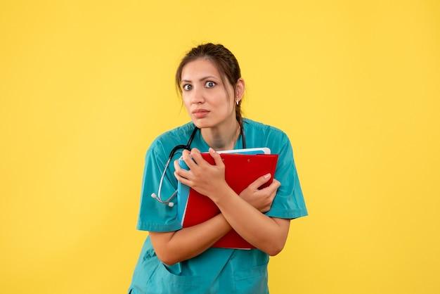 Widok z przodu kobieta lekarz w koszuli medycznej gospodarstwa analizy na żółtym tle