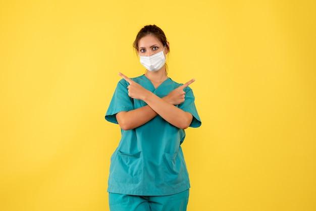 Widok z przodu kobieta lekarz w koszuli medycznej i masce na żółtym tle
