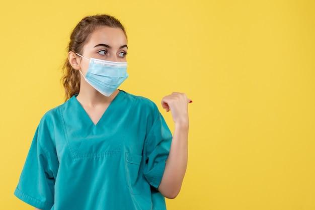 Widok z przodu kobieta lekarz w koszuli medycznej i sterylnej masce, choroba koronawirusa jednolity wirus covid-19 pandemia zdrowia