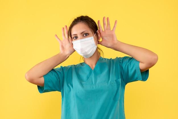 Widok z przodu kobieta lekarz w koszuli medycznej i sterylnej masce na żółtym tle