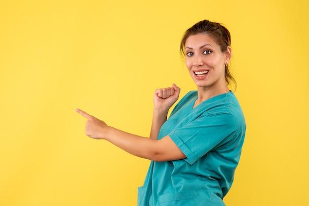Widok z przodu kobieta lekarz w koszuli medycznej na żółtym biurku wirus szpitala medyk pielęgniarka zdrowie kolor choroby