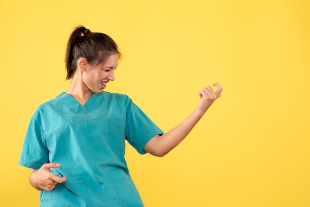 Widok z przodu kobieta lekarz w koszuli medycznej na żółtym tle