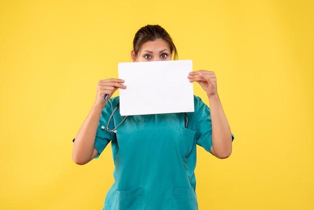 Widok z przodu kobieta lekarz w koszuli medycznej trzymając analizę papieru na żółtym tle