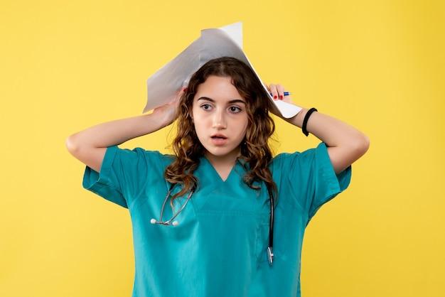 Widok z przodu kobieta lekarz w koszuli medycznej trzymając papierową analizę na żółtym biurku pandemiczny wirus zdrowia jednolity covid-19 emocja