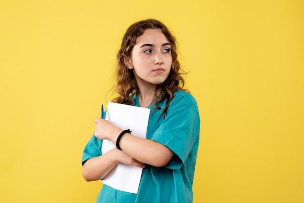 Widok z przodu kobieta lekarz w koszuli medycznej trzymającej analizę papieru, mundur wirusowy covid-19 emocja pandemiczna zdrowia