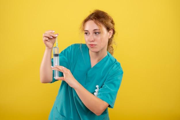 Widok z przodu kobieta lekarz w koszuli medycznej z zastrzykiem, kolorowy wirus pandemii covid-19 zdrowia emocji