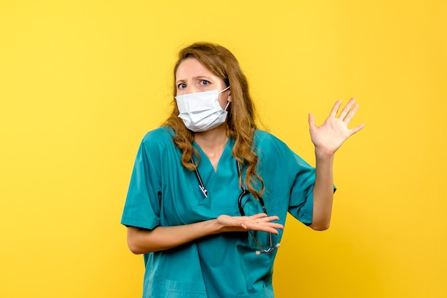 Widok z przodu kobieta lekarz w masce na żółtej przestrzeni