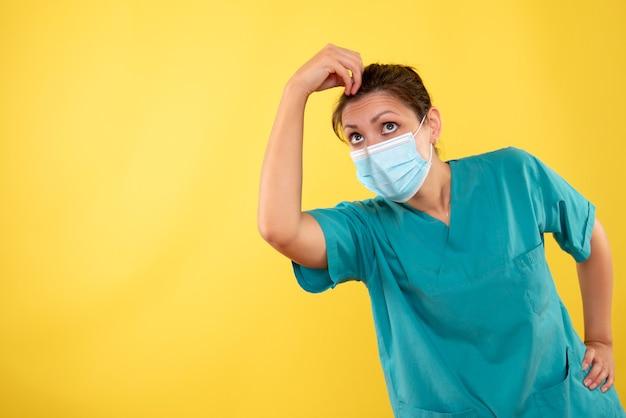 Widok z przodu kobieta lekarz w masce ochronnej na żółtym tle