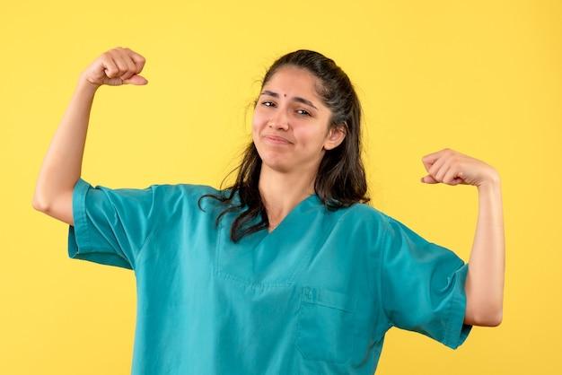 Widok z przodu kobieta lekarz w mundurze pokazujący mięśnie w pozycji stojącej