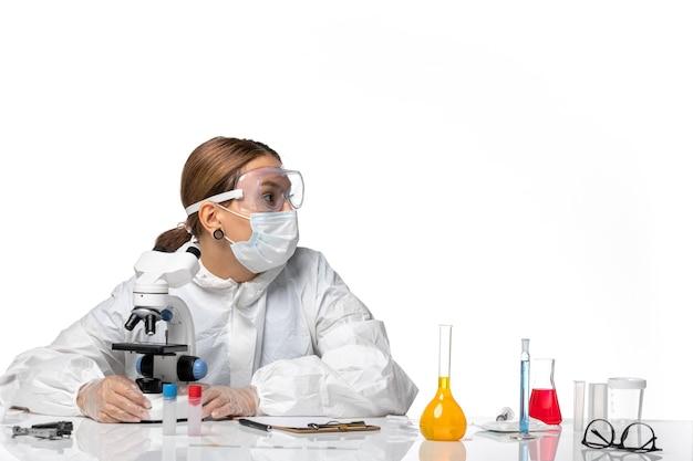 Widok z przodu kobieta lekarz w specjalnym garniturze i noszącej maskę za pomocą mikroskopu na białym tle koronawirus pandemiczny wirusa pandemii