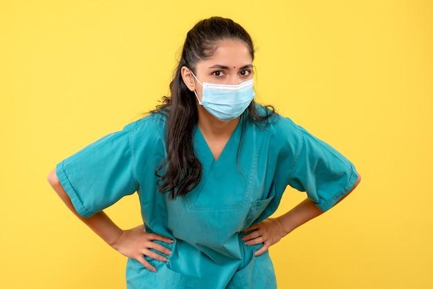 Widok z przodu kobieta lekarz z maską medyczną, kładąc ręce
