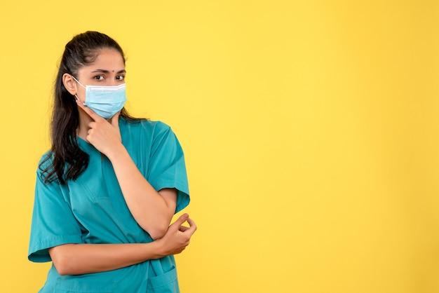 Widok z przodu kobieta lekarz z maską medyczną, kładąc rękę