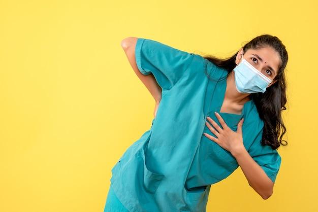 Widok z przodu kobieta lekarz z maską, trzymając ją z powrotem, oddając rękę