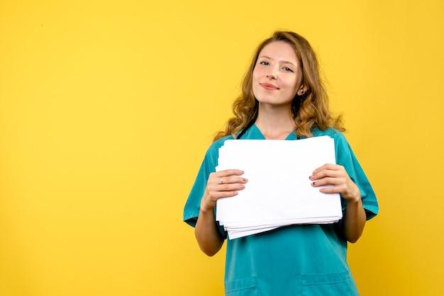 Widok z przodu kobieta lekarz z plikami na żółtej podłodze wirus medyczny szpitala emocji