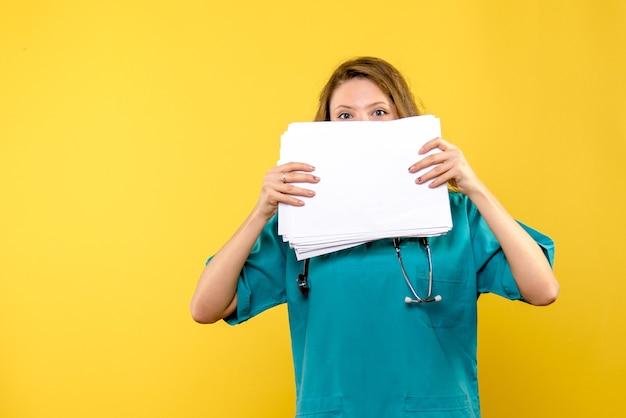 Widok z przodu kobieta lekarz z plikami na żółtej przestrzeni