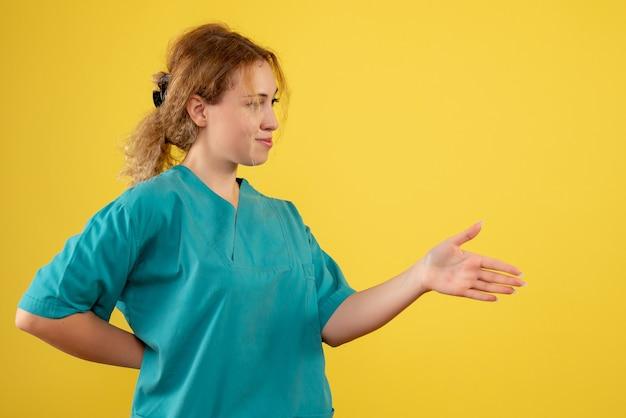Widok z przodu kobieta lekarz z pozdrowieniami medycznej koszuli, pielęgniarka medyczna zdrowia covid-19 kolor