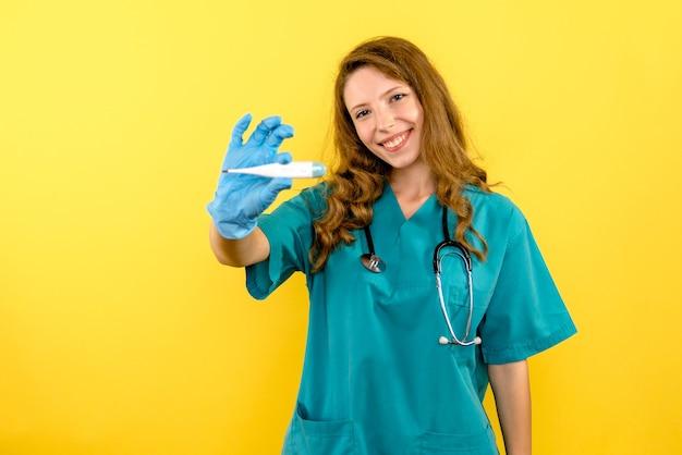 Widok z przodu kobieta lekarz z urządzeniem do pomiaru temperatury na żółtej przestrzeni