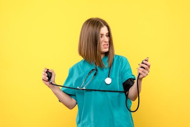 Widok z przodu kobieta lekarz za pomocą tonometru na jasnożółtej przestrzeni