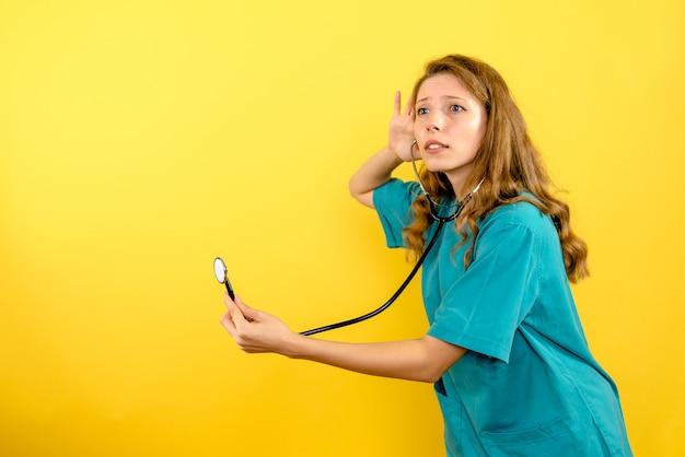Widok z przodu kobieta lekarz ze stetoskopem na jasnożółtej przestrzeni